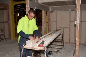 Image of a student cutting 55mm cove cornice in a mitre box on a bench set up using planks and trestles
